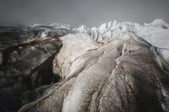 De close-upbarst is een diepe blauwe die barst in de ijskap en de zwarte modder op de gletsjer wordt gevonden Brede hoek en drama stock fotografie
