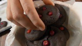 De close-uphand neemt chocoladekoekjes van een pan stock footage