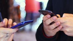 De close-uphand van de mens en vrouw gebruikt mobiele telefoon in sneeuwavond, die met vrienden, lichten en decoratie chating voo stock videobeelden