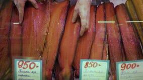 De close-uphanden zet gerookte gezouten rode zalm in winkelvenster bij vissenmarkt stock videobeelden