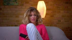 De close-uphuisvrouw in roze sweater schakelt de film met ver controlemechanisme en horloges aandachtig bij comfortabel huis in stock footage