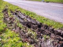 De close-upmening van autowiel volgt sporen in modder naast Britse weg royalty-vrije stock foto's