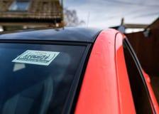 De close-upmening van een gezien alarmwaarschuwingsbord maakte aan de voorruit op een nieuw hybride voertuig vast royalty-vrije stock foto's