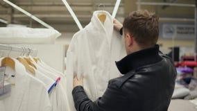 De close-upmening van een jonge mens in een leerjasje kiest een badjas in de opslag van bedlinnen en toebehoren stock videobeelden