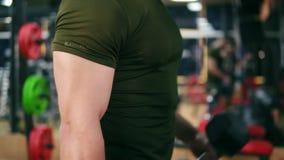 De close-upmening van een sportief mensen` s sterke hand die dumbell krult oefeningen in gymnastiek doen Geschoten in 4k stock footage