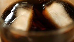 De close-upmening van glas met donkere cocktaildranken en ijsblokjes daarin die borrelt maken Stock Foto