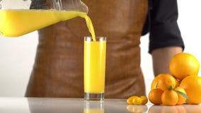 De close-upmening van het jus d'orange die in het hoge glas vallen plaatste dichtbij mandarins stock videobeelden