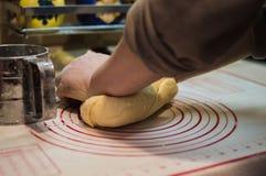 De close-upmening van het wijfje overhandigt het kneden tarwedeeg voor de eigengemaakte cake Stock Afbeeldingen