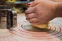 De close-upmening van het wijfje overhandigt het kneden tarwedeeg voor de eigengemaakte cake Stock Foto's