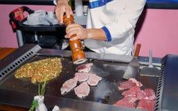 De close-upmening van Nice van mens, persoonshanden die uitstekende oude houten peperschudbeker boven vers kokend vlees houden royalty-vrije stock afbeeldingen