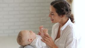 De close-upmoeder speelt met haar pasgeboren zoon thuis op het bed stock video