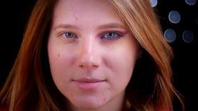 De close-upspruit van het jonge aantrekkelijke Kaukasische vrouwelijke aan het licht brengen paste half make-up toe bekijkend rec stock footage