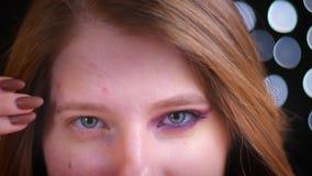 De close-upspruit van het jonge aantrekkelijke Kaukasische vrouwelijke half toegepast aan het licht brengen schittert make-up bek stock videobeelden