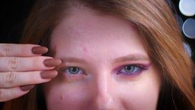De close-upspruit van het jonge aantrekkelijke Kaukasische vrouwelijke half toegepast aan het licht brengen schittert make-up bek stock footage