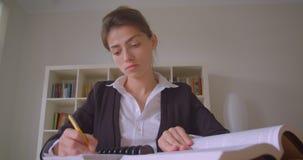 De close-upspruit van het jonge vrij Kaukasische vrouwelijke student nemen neemt nota van het bekijken camera in de universitaire stock footage