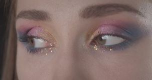 De close-upspruit van jong leuk Kaukasisch kort haired vrouwelijk gezicht met schittert make-up bekijkend camera met achtergrond stock video