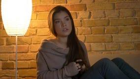 De close-upspruit van jong leuk Kaukasisch wijfje die op een TV letten toont wordt gefascineerd in een comfortabele flat stock foto's