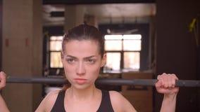 De close-upspruit van jonge aantrekkelijke atleet vrouwelijke het opheffen gewichten en het maken hurkt voor de camera in de gymn stock video