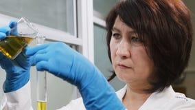 De close-upvrouw giet gele vloeistof in buis in laboratorium stock video