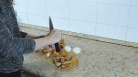 De close-upvrouw overhandigt schoon een ui van de schil op de keukenlijst Zachte nadruk stock video