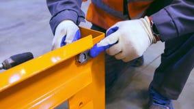 De close-upwerknemer verdraait schroef bij de metaalbouw stock video