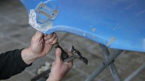 De close-upwerktuigkundige richt deuken op de kap van de machine Het schilderen van de auto stock footage