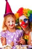De clown die van het verjaardagskind cake met jongen samen eten Jong geitje met slordig gezicht Royalty-vrije Stock Foto