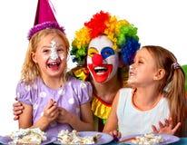 De clown die van het verjaardagskind cake met jongen samen eten Jong geitje met slordig gezicht Stock Afbeeldingen