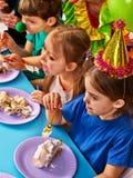 De clown die van het verjaardagskind cake met jongen samen eten Jong geitje met slordig gezicht Royalty-vrije Stock Foto's