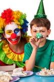De clown die van het verjaardagskind cake met jongen samen eten Jong geitje met slordig gezicht Stock Foto