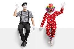 De clown en bootst zitting op een paneel en het golven na stock foto's
