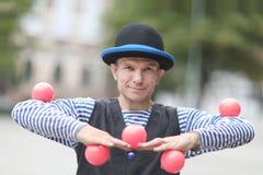De clown jongleert met met roze ballen stock afbeeldingen