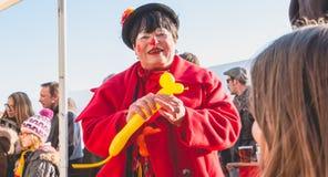 De clown maakt karakters met ballen om hen aan de kinderen aan te bieden Stock Foto