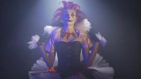 De clownvrouw met schitterende make-up zit onder de schijnwerper van het circus en past de kraag van haar kleding aan stock videobeelden