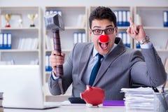 De clownzakenman met een spaarvarken en een hamer Stock Afbeelding