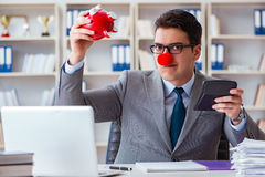 De clownzakenman met spaarvarken die boekhouding doen Royalty-vrije Stock Fotografie
