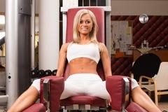 De club van de gymnastiekgeschiktheid binnen met jonge vrouwen die gewichten met benen opleiden royalty-vrije stock afbeeldingen