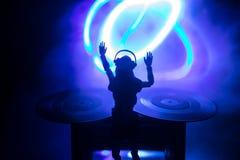 De clubconcept van DJ Vrouw DJ die, en in een Nachtclub mengen zich krassen Meisjessilhouet op het dek van DJ \ 's, stroboscoopli royalty-vrije stock foto