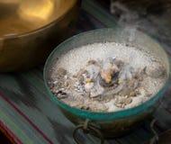 _de cobre cuenco llenar con arena y grava, en que uno pedazo incienso brillar intensamente y fumar fotos de archivo