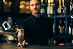 De cocktail is op de barteller De barman is op achtergrond royalty-vrije stock foto's