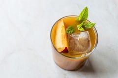 De Cocktail van de perzikbourbon met Perzikplak, Muntbladeren en Ijs stock foto's