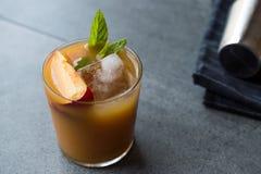 De Cocktail van de perzikbourbon met Perzikplak, Muntbladeren en Ijs stock afbeelding