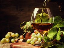 De cognac giet in Glas, Druiven en Wijnstok, Uitstekende Houten Achtergrond, royalty-vrije stock afbeeldingen