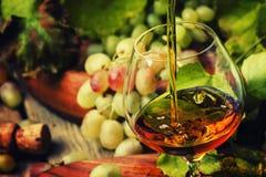 De cognac giet in Glas, Druiven en Wijnstok, Uitstekende Houten Achtergrond, stock foto