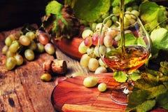 De cognac giet in Glas, Druiven en Wijnstok, Uitstekende Houten Achtergrond, stock fotografie