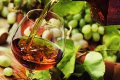 De cognac giet in Glas, Druiven en Wijnstok, Uitstekende Houten Achtergrond, royalty-vrije stock foto's