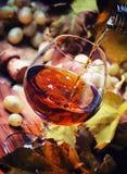 De cognac giet in Glas, Druiven en Wijnstok, Uitstekende Houten Achtergrond, stock foto's