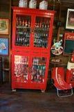 De cokes in een mooi rood kabinet wordt gevestigd op een houten vloer royalty-vrije stock afbeeldingen