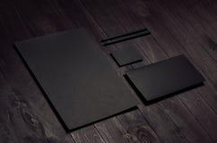 De collectieve identiteitsreeks van leeg zwart briefhoofd, envelop, adreskaartje op donkere houten raad, neigde Stock Afbeeldingen