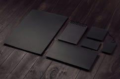 De collectieve identiteitsreeks van leeg zwart briefhoofd, envelop, blocnote, adreskaartje op donkere houten raad, neigde Stock Foto's